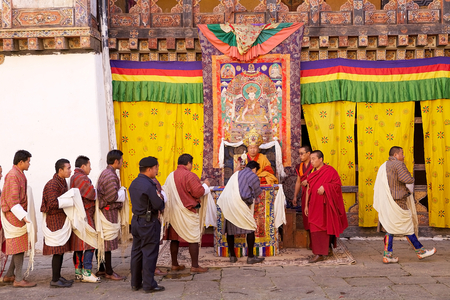 venerable: Venerable buddhist monk is blessing bhutanese people in traditional clothes during the celebration for the birthday of the 4th King of Bhutan at the Trongsa Dzong, Trongsa, Bhutan. Trongsa Dzong is the largest dzong fortress in Bhutan. A temple was first