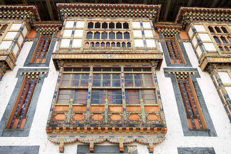 frontage: Wooden frontage with small arched windows at the Kurjey Lhakhang also known as Kurjey Monastery, located in the Bumthang Valley in the Bumthang District, Bhutan. This is the final resting place of the first three King of Bhutan. Also, a large tree behind  Stock Photo