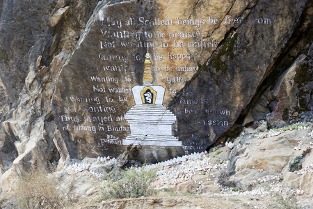 offerings: Votive offerings at the rock painting along the road from Trongsa to Pele La Pass, Bhutan