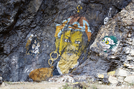 votive: Votive offerings at the rock painting along the road from Trongsa to Pele La Pass, Bhutan