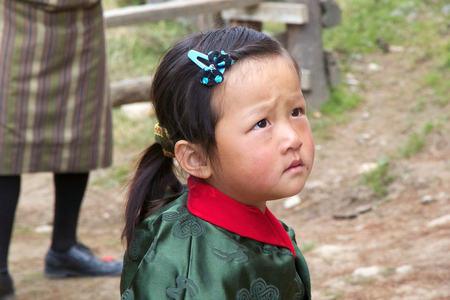 median age: Bhutanese child with traditional clothes  at the Gangteng village, Phobjikha Valley, Bhutan. Bhutan has a population of less than 1 million people and the Bhutanese people has a median age of 24.8 years