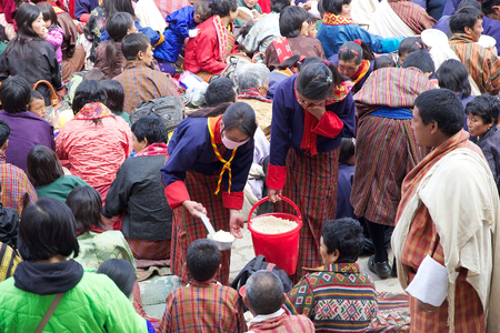 necked woman: Young Bhutanese women are distributing food at the people who are attending at the ceremony during the Black-necked crane Festival at the Gangtey Monastery also known as Gantey Gompa, Gangten, Bhutan. Gangtey Monastery is an important monastery of Nyingma