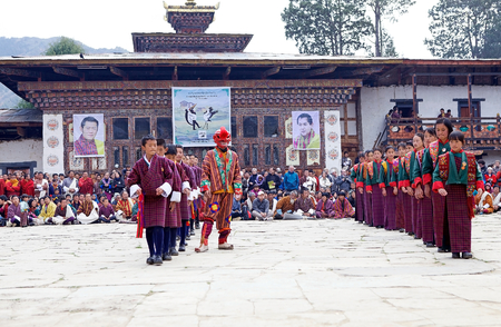 rom: Dancers, teenagers rom the primary school, with traditional clothes and masked clown, Atsaras, are performing the Rigsar dance during the Black-necked crane Festival at the Gangtey Monastery also known as Gantey Gompa, Gangten, Bhutan. The masked clown wh Editorial