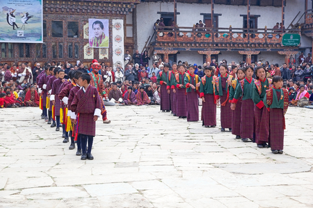 gompa: Dancers, children from the primary school, with traditional clothes are performing the Rigsar dance during the Black-necked crane Festival at the Gangtey Monastery also known as Gantey Gompa, Gangten, Bhutan. Gangtey Monastery is an important monastery of Editorial