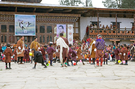 blasting: Children from the local community with traditional clothes are performing the Balloon blasting competition during the Black-necked crane Festival at the Gangtey Monastery also known as Gantey Gompa, Gangten, Bhutan. Gangtey Monastery is an important monas