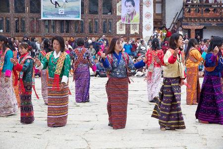 necked woman: Dancers, women from the local community, with traditional clothes  are performing the Boedra dance during the Black-necked crane Festival at the Gangtey Monastery also known as Gantey Gompa, Gangten, Bhutan. Gangtey Monastery is an important monastery of