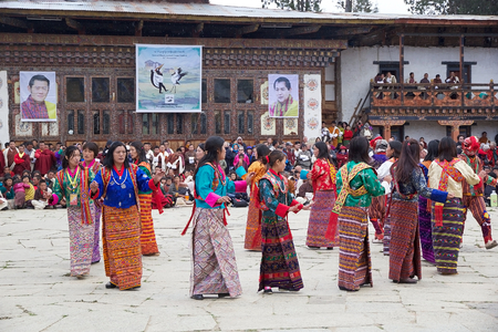 necked woman: Dancers, women from the local community, with traditional clothes and masked clown, Atsaras, are performing the Boedra dance during the Black-necked crane Festival at the Gangtey Monastery also known as Gantey Gompa, Gangten, Bhutan. The masked clown who  Editorial