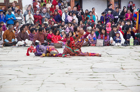 Masked clowns, Atsaras, are mimic the dancers at the Black-necked crane Festival at the Gangtey Monastery also known as Gantey Gompa, Gangten, Bhutan. The masked clowns who mimic the dancers and people are the only one who is allowed to mock religious dan