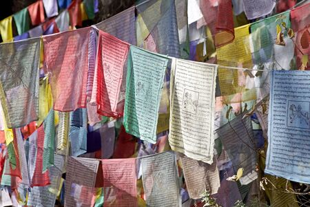 praye: Prayer flags along the footpath to the Tigers Nest, Paro, Bhutan. The flags do not carry prayers to God, but the prayers are blowed into the wind to spread the good will and compassion into all pervading space. Praye flags come in set of five, one fin ea Stock Photo