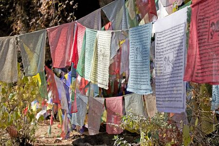 blowed: Prayer flags along the footpath to the Tigers Nest, Paro, Bhutan. The flags do not carry prayers to God, but the prayers are blowed into the wind to spread the good will and compassion into all pervading space. Praye flags come in set of five, one fin ea Stock Photo