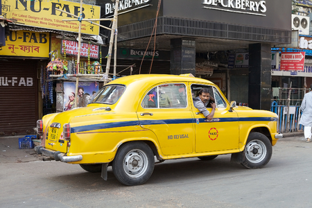 out of production: A local taxi driver is driving along the street around Hogg Market, Kolkata, India. The metered-cabs are mostly of the brand Ambassador manufactured by Hindustan Motors, now out of production. Editorial