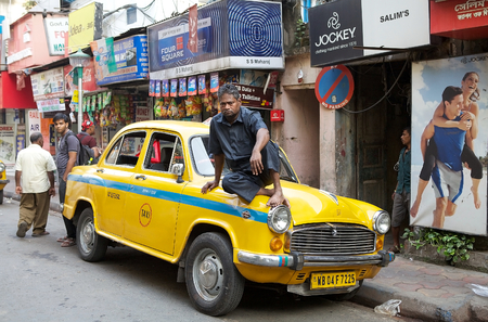 ambassador: A local taxi driver is sitting on the taxi along the street around Hogg Market. The metered-cabs are mostly of the brand Ambassador manufactured by Hindustan Motors, now out of production.