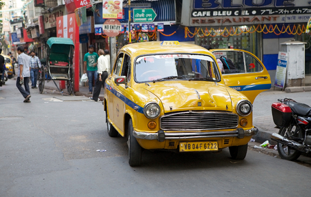 ambassador: Urban scene in Kolkata, India. A local taxi along the street around Hogg Market. The metered-cabs are mostly of the brand Ambassador manufactured by Hindustan Motors, now out of production.