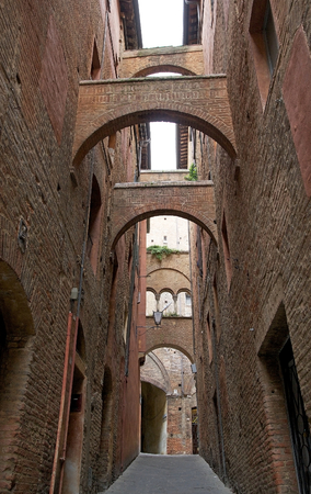 Urban street of old Siena, Tuscany, Italy. The historic centre of Siena has been declared by UNESCO World Heritage Site Stock Photo