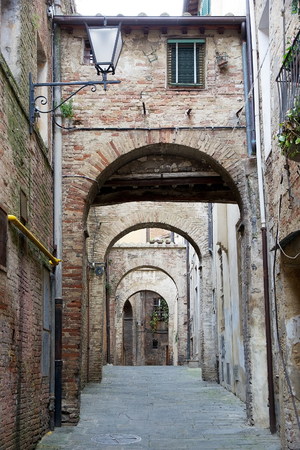declared: Urban street of old Siena, Tuscany, Italy. The historic centre of Siena has been declared by UNESCO World Heritage Site Stock Photo