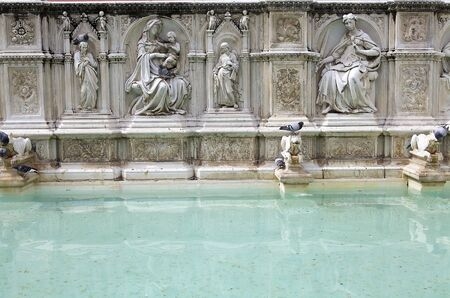 angels fountain: Madonna and child with flanking Angels from Fonte Gaia, Siena, Tuscany, Italy. Fonte Gaia is a monumental fountain located in the Piazza del Campo. It was completed in 1342 and the underground pipes brought water from 25 kilometers away Stock Photo