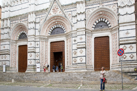 decades: Tourists at the entrance of the Baptistery of San Giovanni, Siena, Tuscany, Italy. The Baptistery of San Giovanni was built below the Cathedral of Siena by master-builder Camaino di Crescentino between the second and third decades of XIV century. The rect