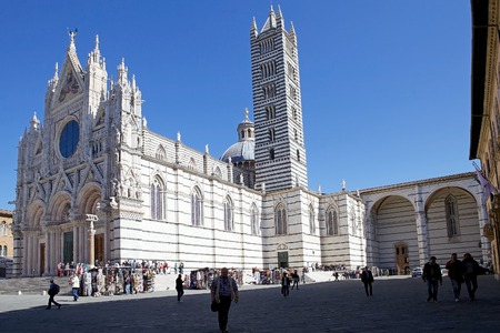 Tourists outside the Siena Cathedral in historic city of Siena, Tuscany, Italy. Siena Cathedral, Metropolitan Cathedral of Saint Mary of the Assumption, was built in 1215-1263 on the site of an earlier structure.