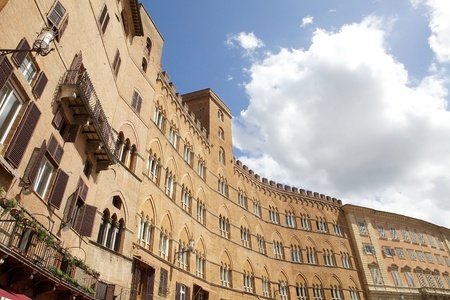 Mansions in Piazza del Campo, the principal public space of the historic centre of Siena, Tuscany, Italy. The mansions that line the shell-shaped square have unified the rooflines.