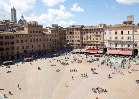 unified: Piazza del Campo view. Piazza del Campo is the principal public space of the historic centre of Siena, Tuscany, Italy. The mansions that line the shell-shaped square have unified the rooflines. The twice a year horse race, Palio di Siena, is held around t
