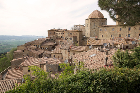 Ancient houses in the historic centre of Volterra with view on the hills, Tuscany, italy. The town was a Bronz Age settlement of the Villanovan Culture and an important Etruscan centre. Stock Photo