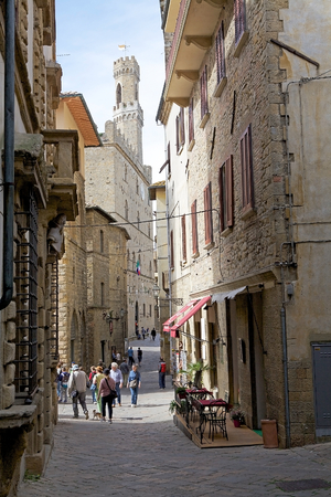 volterra: Tourists are walking along the narrow street with Palazzo dei Priori in the background in the historic centre of Volterra, Tuscany, italy. iPalazzo dei Priori was built in 1208-1257. It is in the Piazza dei Priori, the main square of Volterra, a fine exam