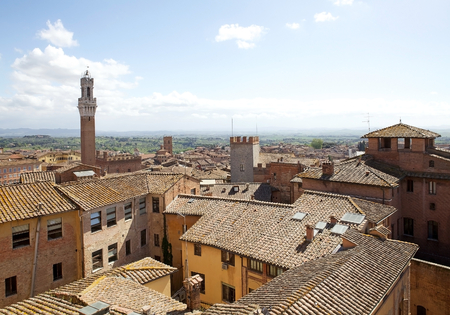historic place: Aerial view of the Torre del Mangia and the historic city of Siena, Tuscany, Italy, with the hills in the background.