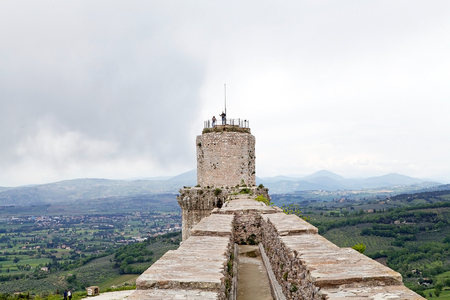 documented: Tourists are visiting the Rocca Maggiore, Assisi, Italy, with panorama. Rocca Maggiore dominated by more than eight hundred years the citadel of Assisi and the valley of Tescio. The first documented regarding the fortress date back to 1173.