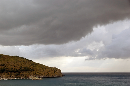 supposedly: Dark clouds over the Cape palinuro, Centola, Italy. Cape Palinuro is located in southwestern Italy, in the Cilento region. It is supposedly named after Palinurus, the helmsman of Aeneas ship in Virgils Aeneid