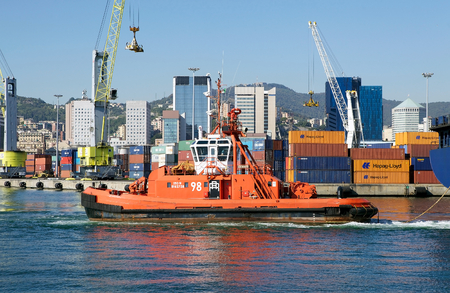 A tugboat with harbour cranes at the Port of Genoa with town buildings in the background, Genoa, Italy. The Port of Genoa is the major italian seaport in the Mediterranean sea. It covers an area of 700 hectares of land and 500 hectares of water