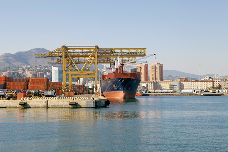 Harbour cranes are loading cargo on a container ship at the Port of Genoa, Italy. The Port of Genoa is the major italian seaport in the Mediterranean sea. It covers an area of 700 hectares of land and 500 hectares of water