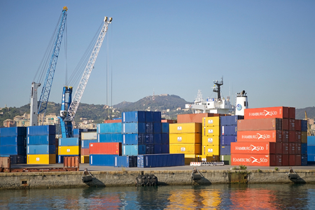 Harbour cranes and containers at the Port of Genoa, Italy. The Port of Genoa is the major italian seaport in the Mediterranean sea. It covers an area of 700 hectares of land and 500 hectares of water