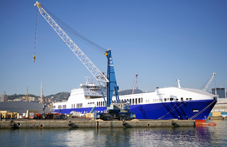Harbour cranes are loading cargo on a general cargo ship at the Port of Genoa, Italy. The Port of Genoa is the major italian seaport in the Mediterranean sea. It covers an area of 700 hectares of land and 500 hectares of water