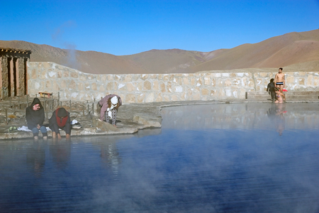 latinamerican: Tourists are taking a bath in a natural swimming pool at the El Tatio geysers, Chile. El Tatio is a geyser field located in the northern Chile. It is the largest geyser field in the southern hemisphere and the third geyser field in the world.