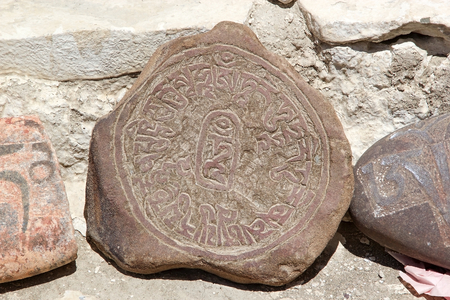 Mani stone at the Stok Palace in Ladakh, India. Mani stone, inscribed with a mantra,  is a form of prayer in Tibetan Buddhism