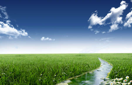 Stream in a grassland with blue sky and clouds
