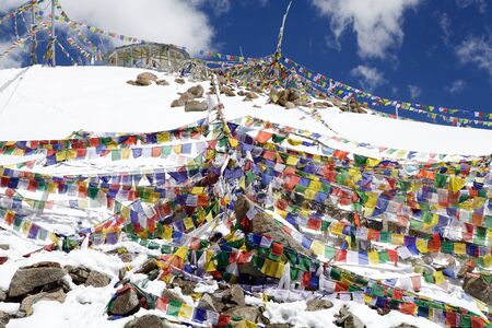 Prayer flags at the Khardung Pass in Ladakh, India. The Khardung Pass is the higest vehicle accessible pass in the world. Stock Photo