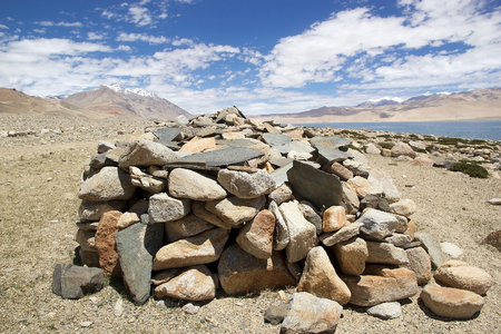 Mani stones at the Tso Moriri Lake In Ladakh region in the Indian state of Jammu and Kashmir. The mountain lake is at an altitude of 4522 m in the Changthang Plateau  Stock Photo