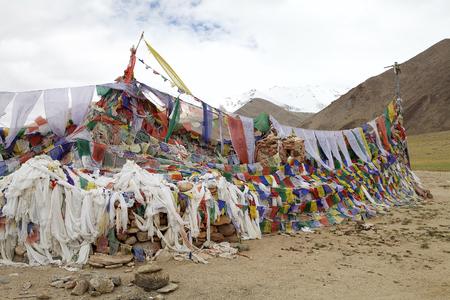 Gebedsvlaggen bij de bergpas langs de weg van Karzok-dorp aan Tsokar-Meer in Ladakh-gebied in de Indische staat van Jammu en Kashmir.