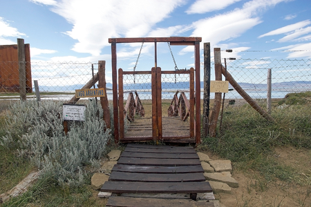 The door to pass from Laguna Nimez, a wildlife reserve at El Calafate, and Lake Argentino, in Patagonia, Argentina. The reserve is a few steps from the city center and close to Lake Argentino. The Laguna Nimez concentrates a varied sample of local wildlif Banco de Imagens - 104684982