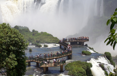 Footbridge and tourists at the Iguazu Falls, from the Brazil side. Iguazu Falls are waterfalls of Iguazu River on the border of the Argentine province of Misiones and the Brasilian state of Parana Editorial