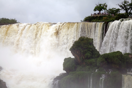 Footbridge and tourists at the Iguazu Falls, from the Argentine side. Iguazu Falls are waterfalls of Iguazu River on the border of the Argentine province of Misiones and the Brasilian state of Parana