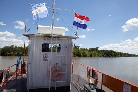 Argentina and Paraguay flags on the boat along the border on the the Parana river, Argentina and Paraguay