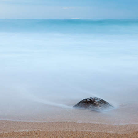 burried: Photo of a rock on a beach, burried in the send and covered by the ocean. Long exposure. Copy space.