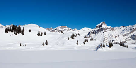 Panoramic photo of snow covered mountains on a bight day with deep blue sky in the Swiss Alps  Stock Photo