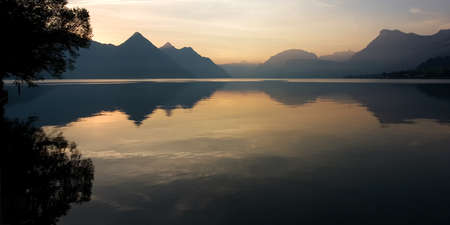 Lake reflection on a beautiful summer sunrise, in the Swiss Alps. Buochs, Switzerland. Stock Photo