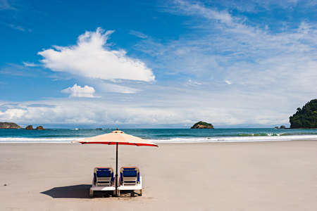 Two chairs and umbrella at the beach. Manuel Antonio, Costa Rica. Stock Photo