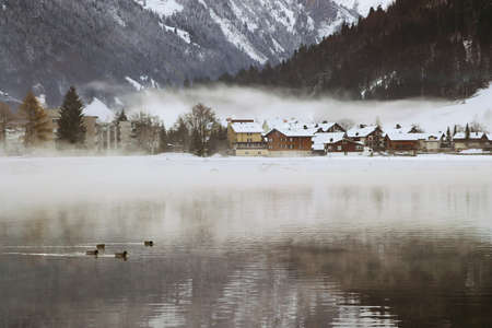 View over a Swiss Village by a lake in the Alps, covered in snow during winter. Stock Photo