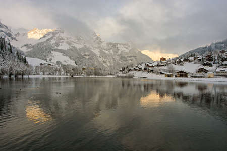 snow covered mountain: View over a Swiss Village by a lake in the Alps, covered in snow during winter. Stock Photo