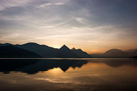 Lake reflection on a beautiful summer day, at sunrise in the Swiss Alps. Buochs, Switzerland. Stock Photo